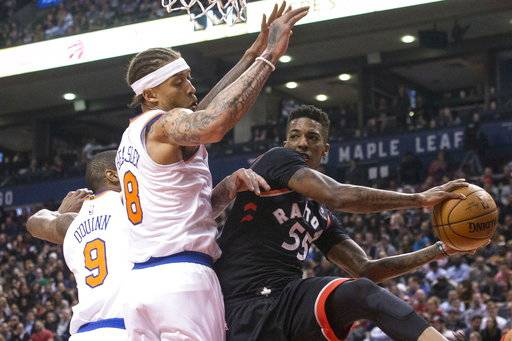 Toronto Raptors' Delon Wright passes the ball as New York Knicks' Michael Beasley, middle, and Kyle O'Quinn defend during the first half of an NBA basketball game Thursday, Feb. 8, 2018, in Toronto. (Chris Young/The Canadian Press via AP)