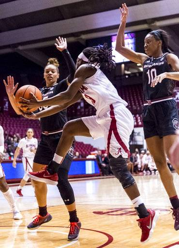 Alabama guard Coco Knight (13) gets off a scoop-shot between South Carolina forward Alexis Jennings (35) and guard Bianca Jackson (10) during an NCAA college basketball game Thursday, Feb. 8, 2018, in Tuscaloosa, Ala. (Vasha Hunt/AL.com via AP)