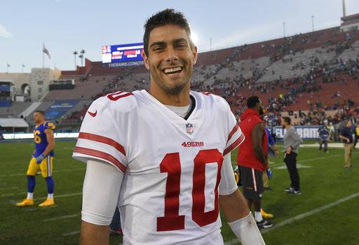 FILE - In this Dec. 31, 2017, file photo, San Francisco 49ers quarterback Jimmy Garoppolo smiles as he walks off the field after the team's 34-13 win over the Los Angeles Rams in an NFL football game in Los Angeles. Garoppolo has signed a five-year contract with the 49ers worth a reported record-breaking $137.5 million. Garoppolo reached the deal on Thursday, Feb. 8, 2018, allowing the Niners to lock up their franchise quarterback without using the franchise tag and before he could become a free agent next month.