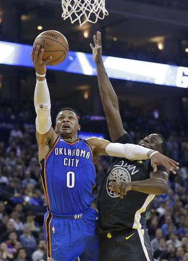 Oklahoma City Thunder's Russell Westbrook (0) drives to the basket as Golden State Warriors' Draymond Green defends during the first half of an NBA basketball game Tuesday, Feb. 6, 2018, in Oakland, Calif.