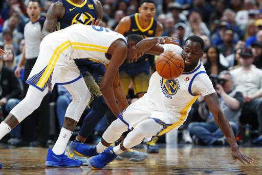 Golden State Warriors forward Kevin Durant, left, collides with forward Draymond Green, who tries to pick up a loose ball during the second half against the Denver Nuggets in an NBA basketball game Saturday, Feb. 3, 2018, in Denver. The Nuggets won 115-108.