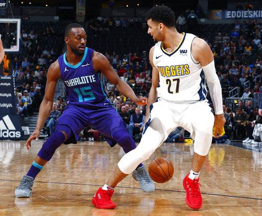Charlotte Hornets guard Kemba Walker, left, knocks the ball away from Denver Nuggets guard Jamal Murray as he drives to the rim in the second half of an NBA basketball game Monday, Feb. 5, 2018, in Denver. The Nuggets won 121-104.
