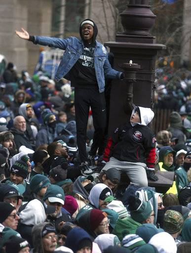A Philadelphia Eagles fan cheers after climbing a light pole during the Eagles team parade and celebration Thursday Feb. 8, 2018, in Philadelphia. The Eagles defeated the New England Patriots in Super Bowl 52.