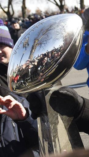 Philadelphia Eagles NFL football head coach Doug Pederson carries the Lombardi Trophy past fans along the parade route during the Super Bowl LII victory parade, Thursday, Feb 8, 2018, in Philadelphia.