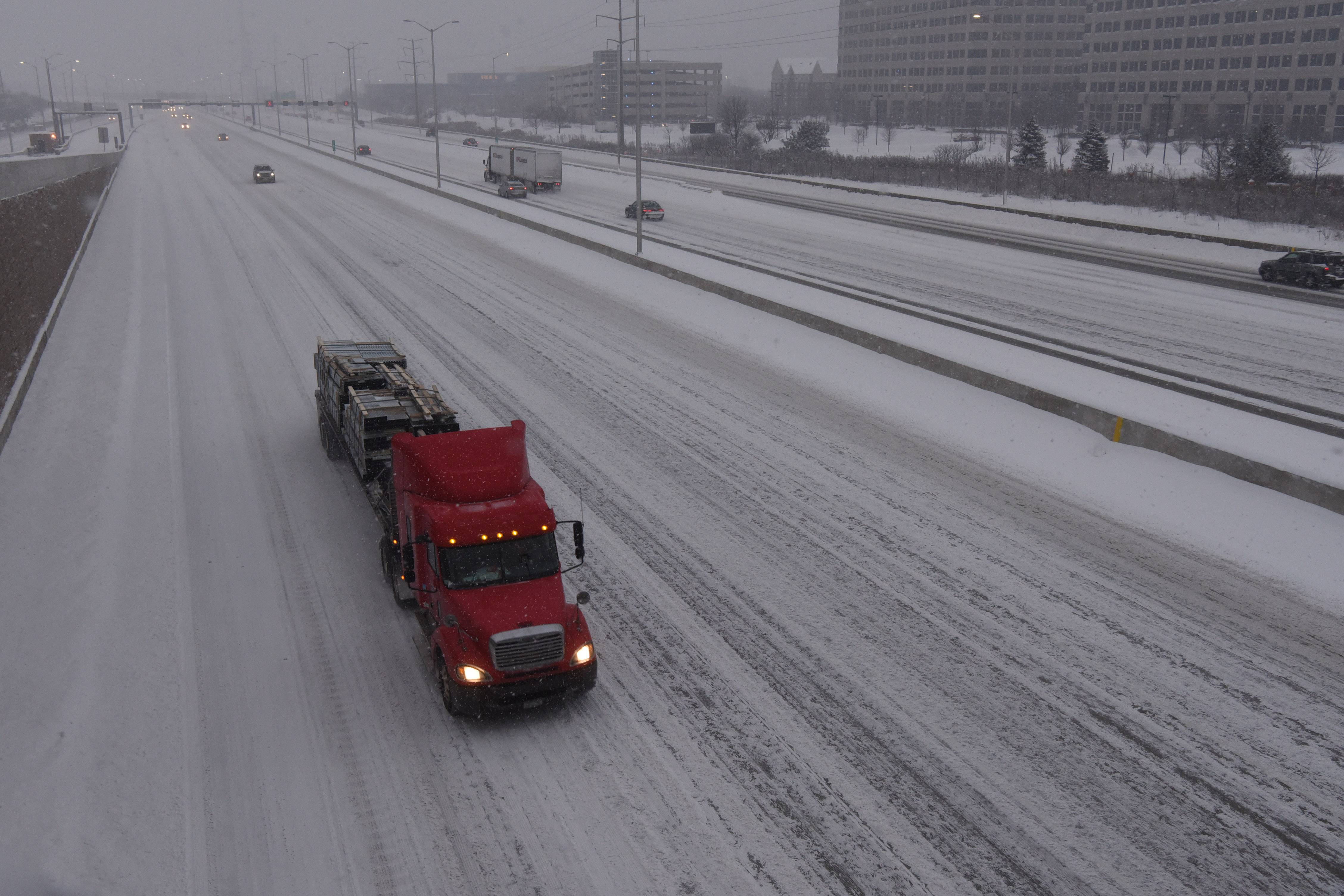A truck carries a load of steel rolls westbound in a snowstorm on Interstate 90 at Meacham Road in Schaumburg during Friday morning's rush hour.