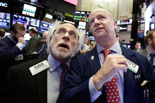 Traders Peter Tuchman, left, and Patrick Casey work on the floor of the New York Stock Exchange, Thursday, Feb. 8, 2018. U.S. stocks are lower Thursday morning as losses from the previous day continue.