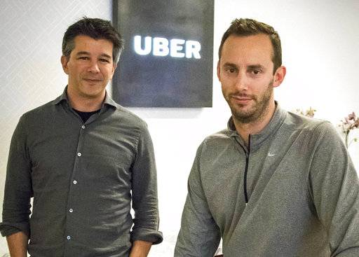 FILE - In this Aug. 18, 2016, file photo, Uber CEO Travis Kalanick, left, and Anthony Levandowski, co-founder of Otto, pose for a photo in the lobby of Uber headquarters in San Francisco. Uber has settled a lawsuit alleging that it ripped off self-driving car technology from Google's autonomous vehicle division, both confirmed the settlement Friday, Feb. 9, 2018. In the lawsuit, Waymo contended that former Uber CEO Kalanick teamed up with ex-Google engineer Levandowski to steal LIDAR laser sensor technology.