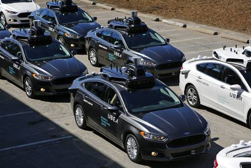 FILE- This Sept. 12, 2016, file photo, shows group of self driving Uber vehicles position themselves to take journalists on rides during a media preview at Uber's Advanced Technologies Center in Pittsburgh. Uber is settling a lawsuit filed by Google's autonomous car unit alleging that the ride-hailing service ripped off self-driving car technology. Both sides in the case issued statements confirming the settlement Friday, Feb. 9, 2018, morning in the midst of a federal court trial in the case.