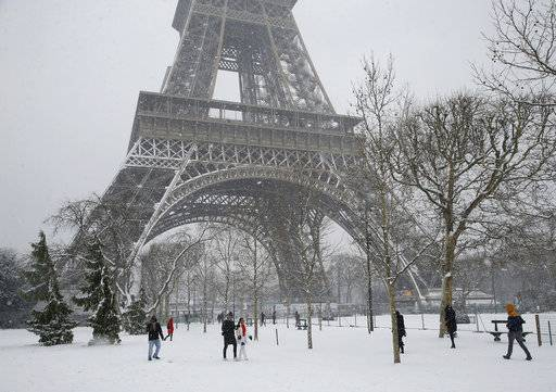 People stroll on the snow-covered Champ de Mars during a snowfall in Paris, France, Friday, Feb. 9, 2018. The Eiffel Tower is closed and authorities are telling drivers in the Paris region to stay home as snow and freezing rain have hit a swath of France ill-prepared for the wintry weather.