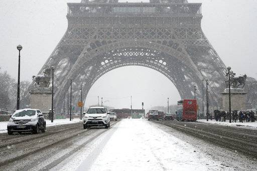 Cars drive over Iena bridge during a snowfall in Paris, France, Friday, Feb. 9, 2018. The Eiffel Tower is closed and authorities are telling drivers in the Paris region to stay home as snow and freezing rain have hit a swath of France ill-prepared for the wintry weather.