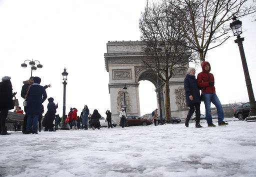 Tourists stroll on the snow-covered Champs Elysees avenue near the Arc de Triomphe in Paris, France, Friday, Feb. 9, 2018. The Eiffel Tower is closed and authorities are telling drivers in the Paris region to stay home as snow and freezing rain have hit a swath of France ill-prepared for the wintry weather.