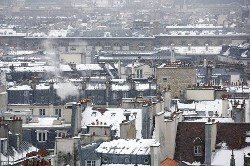 View of the snowy rooftops of Paris, Friday, Feb. 9, 2018. Authorities are telling drivers in the Paris region to stay home as snow and freezing rain have hit a swath of France ill-prepared for the wintry weather.