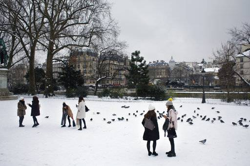 People stroll on the snow covered square in front of Notre Dame cathedral, in Paris, Friday, Feb. 9, 2018. Authorities are telling drivers in the Paris region to stay home as snow and freezing rain have hit a swath of France ill-prepared for the wintry weather.