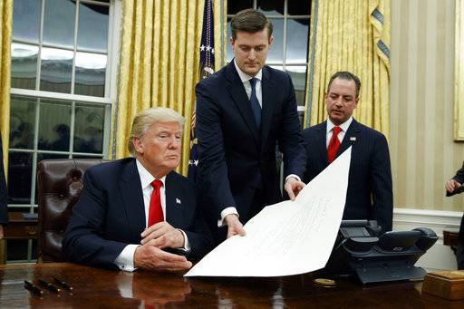 FILE - In this Jan. 20, 2017 file photo, White House Staff Secretary Rob Porter, center, hands President Donald Trump a confirmation order for James Mattis as defense secretary, in the Oval Office of the White House in Washington, as White House Chief of Staff Reince Priebus, right, watches.  Porter is stepping down following allegations of domestic abuse by his two ex-wives.