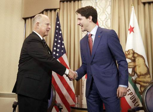 Canada's Prime Minister Justin Trudeau, right, shakes hands with California Gov. Jerry Brown during a meeting in San Francisco, Friday, Feb. 9, 2018.