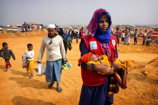 "In this Sunday, Jan. 14, 2018, photo, a volunteer carries a malnourished child from a newly arrived Rohingya family to a transit camp in the Kutupalong refugee camp near Cox's Bazar, Bangladesh. The hunger the Rohingya faced at home is evident when they come to the Bangladesh camps, where new refugees, especially children and women, suffer from ""unbelievable� levels of malnutrition, according to Dr. Ismail Mehr."
