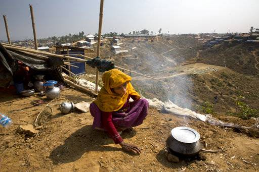 In this Saturday, Jan. 13, 2018, photo, a newly arrived Rohingya woman makes rice for her family at Balukhali refugee camp near Cox's Bazar, Bangladesh.