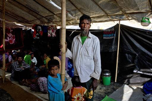 "In this Monday, Jan. 15, 2018, photo, newly arrived Rohingya refugee Mohammad Ilyas, 55, stands in a makeshift transit shelter at the Nayapara camp near Cox's Bazar, Bangladesh. ""They are taking away our paddies, rice, and everything else, to keep us hungry. We were not able to leave our homes or go anywhere safely out of fear of the Buddhists,"" said Mohammad Ilyas, 55, who fled to Bangladesh, with only a shirt and a lungi sarong."