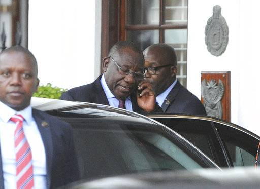 "South African Deputy President Cyril Ramaphosa, on phone, leaves parliament in Cape Town, South Africa, Wednesday, Feb 7, 2018. President Jacob Zuma's exit from power because of scandals appears to be getting closer Ramaphosa, who is expected to replace him, saying he anticipates a ""speedy resolution"" to transition talks he is holding with Zuma."