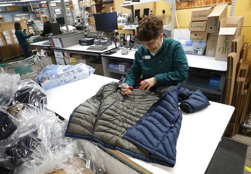 In this Friday, Feb. 2, 2018, photo a worker marks a coat that was returned to the LL Bean retail store in Freeport, Maine. L.L. Bean's generous return policy is going to be a little less forgiving: The company, which has touted its 100 percent satisfaction guarantee for more than a century, is imposing a one-year limit on most returns to reduce growing abuse and fraud.