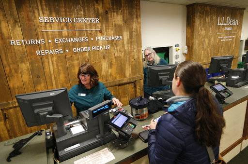 In this Friday, Feb. 2, 2018, photo Dawn Segars accepts a customer's returned items at the LL Bean retail store in Freeport, Maine. L.L. Bean's generous return policy is going to be a little less forgiving: The company, which has touted its 100 percent satisfaction guarantee for more than a century, is imposing a one-year limit on most returns to reduce growing abuse and fraud.