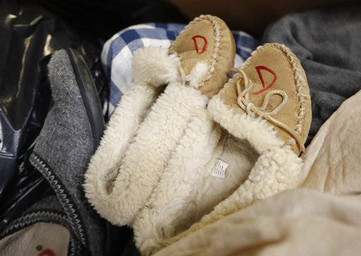In this Friday, Feb. 2, 2018 photo slippers that were returned to the L.L. Bean retail store in Freeport, Maine are marked to prevent future returns. Much of L.L. Bean's returns are donated to Goodwill. L.L. Bean's generous return policy is going to be a little less forgiving: The company, which has touted its 100 percent satisfaction guarantee for more than a century, is imposing a one-year limit on most returns to reduce growing abuse and fraud.