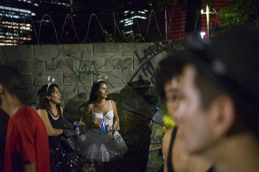 "In this Feb. 8, 2018 photo, revelers attend the street party ""Chroma Aqui na Minha Mao,"" which is a play on words that sounds like ""Eat here from my hand"" in Rio de Janeiro, Brazil. ""The street parties are where the pretty women will be,"" said Television producer Rodrigo Rodrigues, 35. ""Just watching (the schools) parade through the Sambadrome is not the kind of Carnival I want, even if I could afford it."""