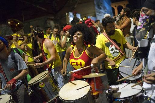 "In this Feb 8, 2018 photo, a woman sporting a Chapulin Colorado costume, from the Mexican television series, drums during the ""Chroma Aqui na Minha Mao"" street party in Rio de Janeiro, Brazil. Compared to the official carnival parades at the Sambadrome where samba schools compete for prizes, street parties are free, or close to it."