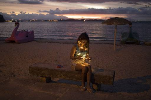 "FILE - In this Feb. 3, 2018 file photo, a reveler wearing lights sits on a bench at dusk as during the ""Perola da Guanabara"" street party on Paqueta island in Guanabara Bay in Rio de Janeiro, Brazil. The local hotel association expects 85 percent of rooms to be taken for Carnival, higher than the last couple years but still far below the nearly maxed-out occupancy of years past."