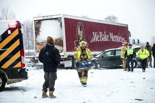 Emergency personnel work at the scene on Interstate 94, Friday, Feb. 9, 2018, near Galesburg, Mich., after scores of vehicles were involved in an accident. (Mark Bugnaski/Kalamazoo Gazette-MLive Media Group via AP)