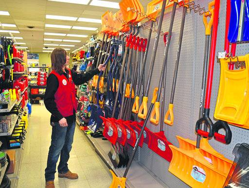 Andrew Brown, assistant manager at Kabelin Ace Hardware, looks through the store's variety of snow shovels ahead of another snowstorm, Thursday, Feb. 8, 2018, in La Porte, Ind. (Jon Gard/The News Dispatch via AP)