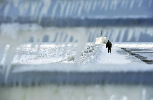 A man walks along the ice-covered south pier Thursday. Feb. 8, 2018, in St. Joseph, Mich. (Don Campbell/The Herald-Palladium via AP)