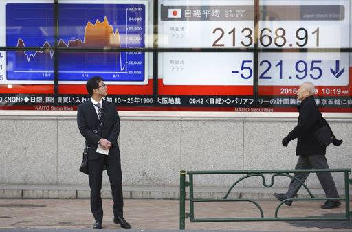 A man looks at an electronic stock board of a securities firm in Tokyo, Friday, Feb. 9, 2018. Asian shares have opened lower and are tracking the overnight plunge on Wall Street.  The Dow Jones industrial average plunged more than 1,000 points as a weeklong market swoon continued.