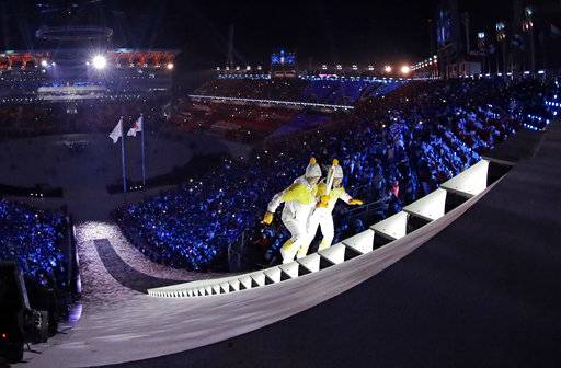 North Korea's Jong Su Hyon, left, and South Korea's Park Jong-ah carry the torch during the opening ceremony of the 2018 Winter Olympics in Pyeongchang, South Korea, Friday, Feb. 9, 2018.