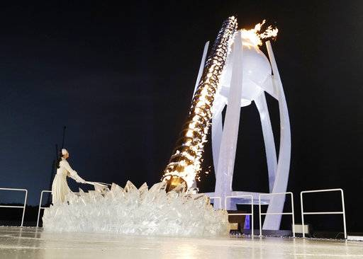 A torchbearer lights the Olympic flame during the opening ceremony of the 2018 Winter Olympics in Pyeongchang, South Korea, Friday, Feb. 9, 2018.