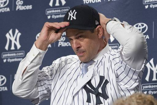 FILE - In this Dec. 6, 2017, file photo, the New York Yankees new manager, Aaron Boone, puts on a Yankees hat during an introductory news conference at Yankee stadium in New York. After reaching Game 7 of the AL Championship Series, the Yankees are back in the familiar position of a favorite. Boone, a rookie manager who succeeded Joe Girardi, has no grace period heading into his first spring training.