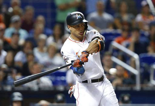 FILE - In this Sept. 4, 2017, file photo, Miami Marlins' Giancarlo Stanton hits a home run during the fifth inning of the team's baseball game against the Washington Nationals, in Miami. The New York Yankees acquired major league home run leader Stanton from the payroll-paring Marlins for All-Star second baseman Starlin Castro and a pair of prospects.