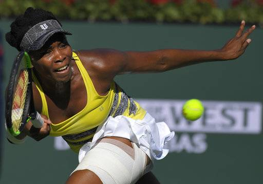 FILE - In this March 13, 2017, file photo, Venus Williams returns a shot to Lucie Safarova, of the Czech Republic, at the BNP Paribas Open tennis tournament, in Indian Wells, Calif. Five months after becoming a mother, Serena Williams is ready to return to competitive tennis for the first time since her 2017 Australian Open title. Williams will join her sister Venus in helping the United States begin its Fed Cup title defense Saturday, Feb. 10, 2018, against the Netherlands.