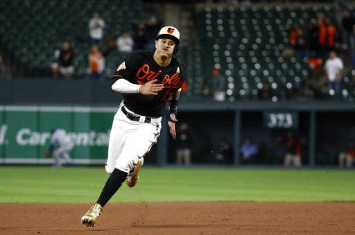 FILE - In this Sept. 1, 2017, file photo, Baltimore Orioles' Manny Machado rounds third base as he runs for home on Jonathan Schoop's double in the 13th inning of a baseball game against the Toronto Blue Jays in Baltimore. Three-time All-Star Manny Machado begins the final season of his contract at a new position: shortstop. Machado moves from third base to the middle of the infield, replacing Tim Beckham, who shifts to third.