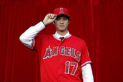 FILE - In this Dec. 9, 2017, file photo, Ls Angeles Angels' Shohei Ohtani, of Japan, poses for photos after a news conference at Angel Stadium, in Anaheim, Calif. Japanese two-way sensation Ohtani signed with the Angels in December following league-wide interest and years of intrigue about the 23-year-old with a powerful right arm and productive bat from the left side of the plate.