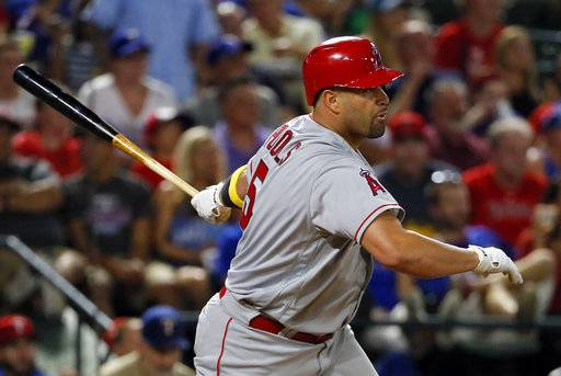 FILE - In this Sept. 1, 2017, file photo, Los Angeles Angels' Albert Pujols follows through on a two-run single that came off a pitch from Texas Rangers starting pitcher Cole Hamels in the fifth inning of a baseball game in Arlington, Texas. Angels' Shohei Ohtani will likely work as part of a six-man starting rotation and then share DH duties with Pujols when not on the mound.