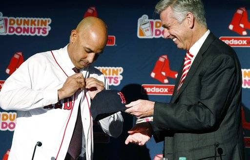 FILE - In this Nov. 6, 2017, file photo, Alex Cora, left, buttons his jersey as he is introduced as the Boston Red Sox's new manager by Dave Dombrowski, the team's president of baseball operations, during a news conference in Boston. Cora takes over for John Farrell, who was fired despite winning the 2013 World Series and two straight AL East championships _ the first back-to-back division titles in franchise history. Cora, 42, is the youngest Red Sox manager in decades, a member of their 2007 championship team and a former teammate of two players on the current roster
