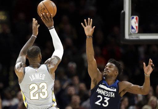 Cleveland Cavaliers' LeBron James, left, shoots over Minnesota Timberwolves' Jimmy Butler for the game-winning basket in overtime of an NBA basketball game, Wednesday, Feb. 7, 2018, in Cleveland. The Cavaliers won 140-138 in overtime.