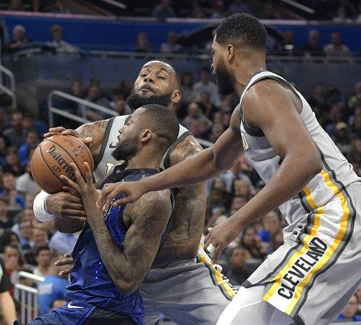 Cleveland Cavaliers forward LeBron James, rear, and center Tristan Thompson defend against Orlando Magic forward Jonathon Simmons during the second half of an NBA basketball game Tuesday, Feb. 6, 2018, in Orlando, Fla. The Magic won 116-98.