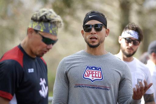 Professional baseball players Jose Lobaton, left, Carlos Gonzalez, center, and Jordan Schafer take a break at the Coach Tom Shaw Performance camp Monday, Jan. 22, 2018, in Lake Buena Vista, Fla.