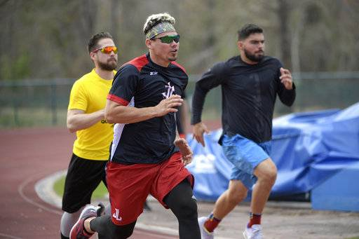 Professional baseball players Jose Lobaton, center, Ender Inciarte, left, and Mauro Conde work out at the Coach Tom Shaw Performance camp Monday, Jan. 22, 2018, in Lake Buena Vista, Fla.