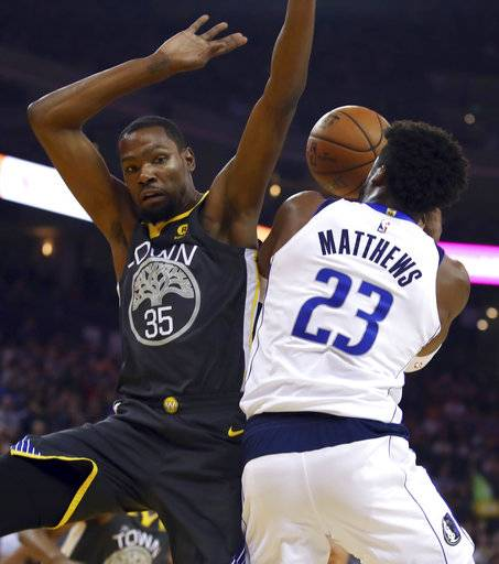 Dallas Mavericks' Wesley Matthews, right, shoots against Golden State Warriors' Kevin Durant (35) during the first half of an NBA basketball game Thursday, Feb. 8, 2018, in Oakland, Calif.