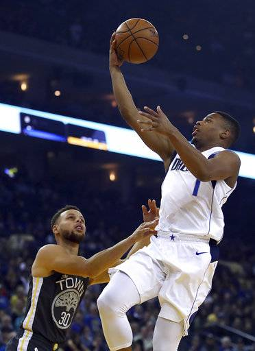 Dallas Mavericks' Dennis Smith Jr., right, lays up a shot over Golden State Warriors' Stephen Curry (30) during the first half of an NBA basketball game Thursday, Feb. 8, 2018, in Oakland, Calif.