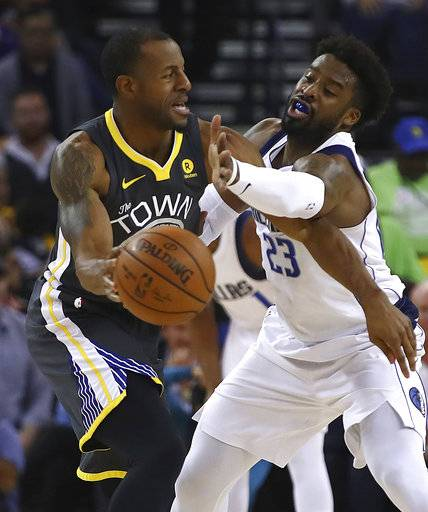 Golden State Warriors' Andre Iguodala, left, looks to pass the ball away from Dallas Mavericks' Wesley Matthews (23) during the first half of an NBA basketball game Thursday, Feb. 8, 2018, in Oakland, Calif.