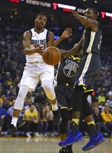 Dallas Mavericks' Dennis Smith Jr., left, passes the ball away from Golden State Warriors' Kevin Durant during the first half of an NBA basketball game Thursday, Feb. 8, 2018, in Oakland, Calif.